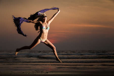 beautiful blonde girl in swimming suit jump with purple scarf on beach on sunset photo