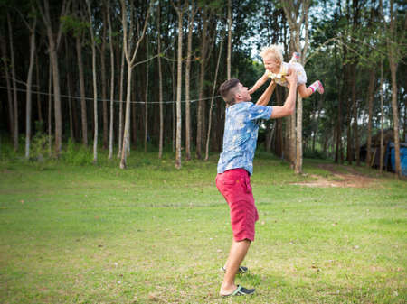 drop off: dad play with his blonde baby daughter drop off her in the sky