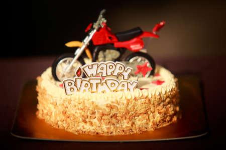 オートバイ図、赤い星と誕生日の言葉で飾られたナッツとバニラ クリームのバースデー ケーキ 写真素材