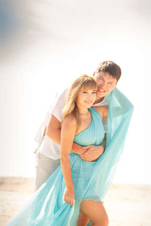 young handsome man hold his beautiful blonde girlfriend in blue dress photo