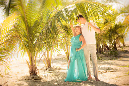 beautiful blonde woman in elegant dress with handsome husband stand in green palm leaves photo