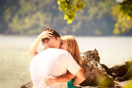 handsome man hold his beautiful blonde wife in elegant dress stand near rock photo