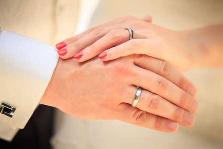 Braut und Bräutigam die Hände mit goldenen Ringen clouseup