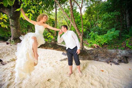 gut aussehend Bräutigam küssen Hand seine blonde Braut im eleganten Hochzeitskleid sitzen auf Baum auf Insel in Thailand Standard-Bild