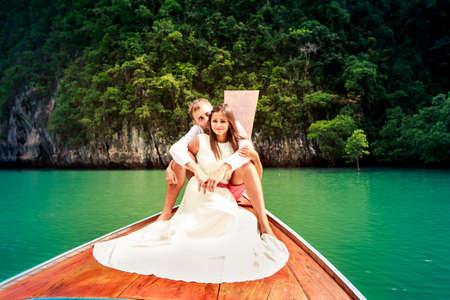 白の結婚式で彼のブルネットの花嫁を抱いてハンサムな新郎ドレスのタイの島のラグーンのロングテール ボートの上に座って 写真素材