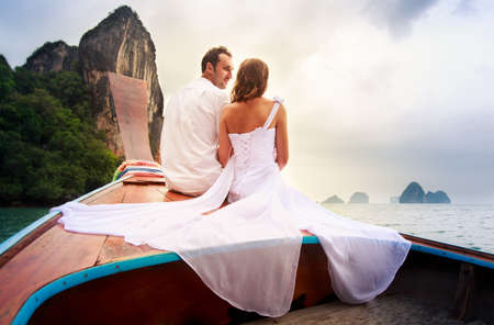 sitt: blonde bride in wedding dress look at handsome groom in white cloth sitting on longtail boat near the rocky island