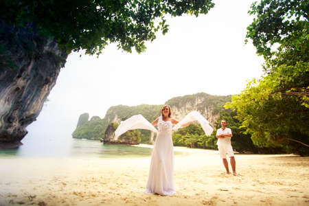 barefoot blonde: handsome groom look at blonde bride waving with veil as wings standing on the sand beach barefoot near green jungle trees Stock Photo