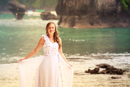 barefoot blonde: young blonde bride demonstrates her wedding dress smile standing barefoot on sandy beach