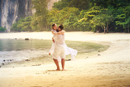 blonde bride and handsome groom whirl and kiss on sandy beach against green cliff and azure sea background photo