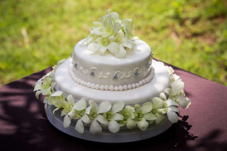 view of large white wedding cake with white orchids and pearls photo