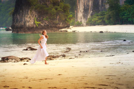 barefoot blonde: young blonde bride smile and run barefoot on sand beach against rocks and azure sea background