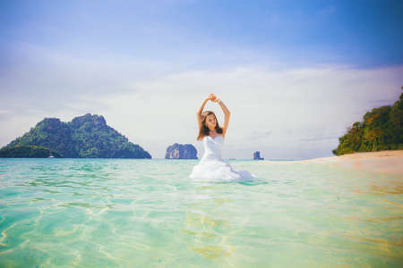 young brunette bride in wedding dress smile playing in shallow azure sea water against rocky islands Stock Photo