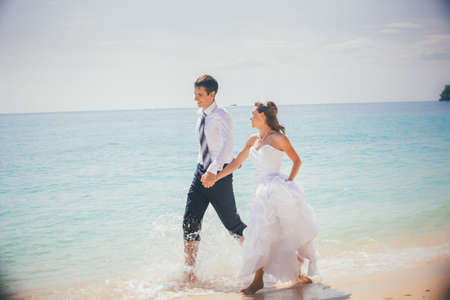 young brunette bride and groom run holding hand in hand on sandy beach in shallow against azure sea and rocky island photo