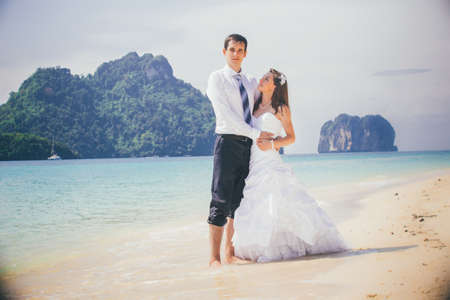 young groom hold his brunette bride standing on sandy beach against azure sea and rocky island photo