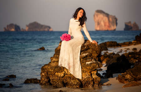 brunette bride sits on rock in sea at beach at sunrise