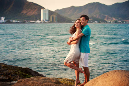 big girl: brunette girl in white dress and guy stand and hug standing on large stone at background of azure sea at dawn Stock Photo