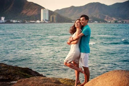 ragazza innamorata: ragazza bruna in abito bianco e basamento ragazzo e abbraccio in piedi sulla grande pietra in sfondo del mare azzurro all'alba