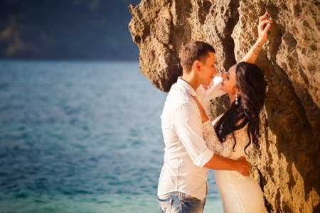 thailand beach: brunette bride and groom lean against rock at beach at sunrise