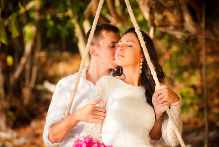 thailand beach: brunette bride and handsome groom roll on rope swing on sand beach of tropical island