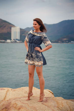 frock: young brunette long-legged girl in short frock with lace barefoot stands tiptoe on stone against sea and resort city