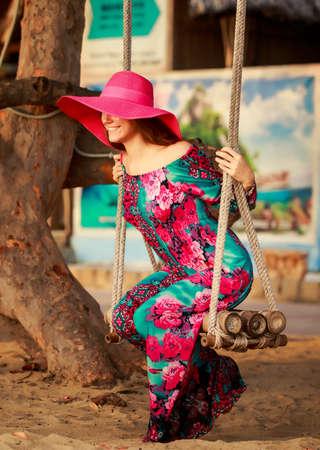 tropical tree: slim brunette longhaired girl in long and big red hat swings on rope swing by tropical tree at defocused background
