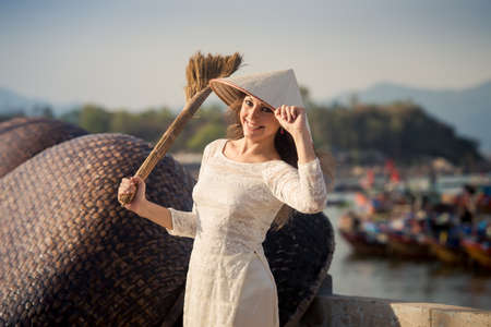 besom: slim blonde girl in Vietnamese national white long dress and hat holds besom on embankment against defocused boats Stock Photo