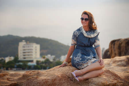 frock: young brunette girl in short grey frock with lace and sunglasses sits on rock and shows legs against resort city