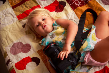 niños rubios: little blonde girl in colorful dress lies on sofa and examines with interest photo camera