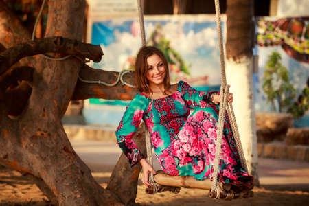 tropical tree: slim brunette longhaired girl in long swings with closed eyes on swing against tropical tree at defocused background