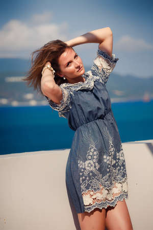 young brunette girl in grey frock with lace smoothes hair by white wall against defocused sea and mountains