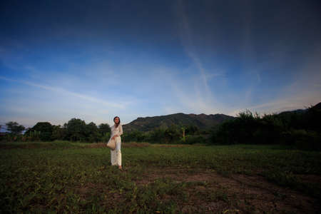 fleecy: slim blonde girl in Vietnamese national white long dress holds hat on field against blue sky and fleecy clouds at sunset