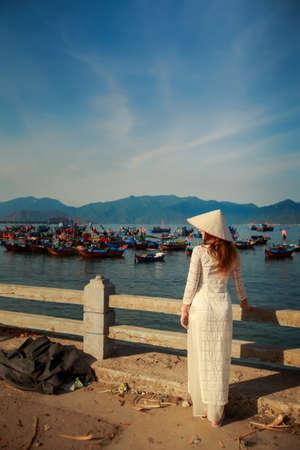 ベトナム国立ホワイト ドレスと帽子裏面観船海に対して堤防でスリムなブロンドの女の子