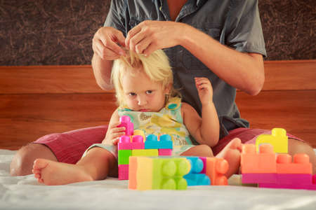 constructor: little blonde girl in colourful dress plays toy constructor and father brushes her hair on sofa