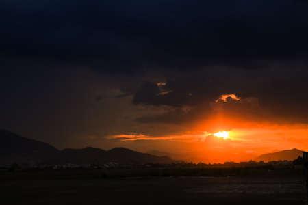 horison: panorama of fantastic sunset above hills resort city and bay Stock Photo
