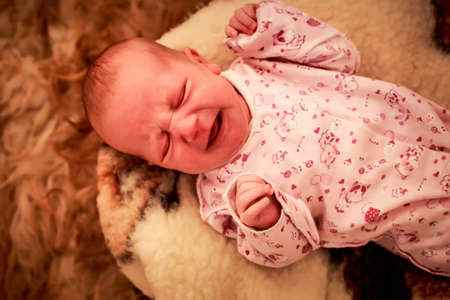 wry: newborn baby closeup cries and makes wry face on round woolen pillow in childish bodysuit