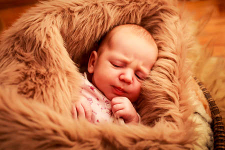 cheek: closeup portrait of newborn baby sleeping face with small hand near cheek covered with brown sheeps