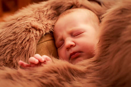 face covered: closeup portrait of newborn baby sleeping face covered with brown sheeps Stock Photo