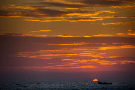 cloud drift: panorama of azure sea and fishing boat drifting against large bright sun disk rising from behind sea Stock Photo