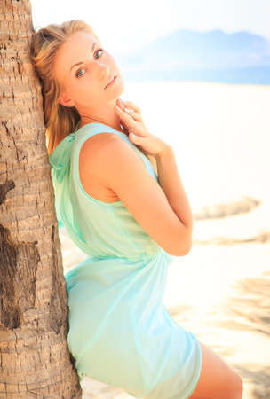 barefoot blonde: european slim sad blonde girl barefoot in light azure transparent frock leans on palm trunk on beach against palms row
