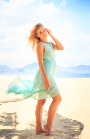 barefoot blonde: european slim blonde girl barefoot in light azure transparent frock stands in palm shadow on beach against sea