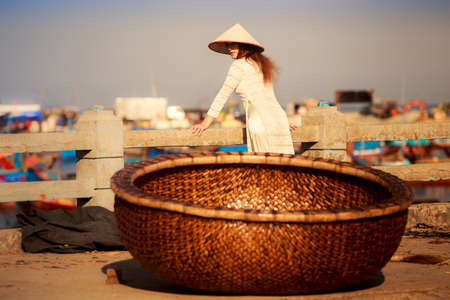 leaning by barrier: view of Vietnamese fishing basket against blonde girl in national dress and hat leaning on barrier against boats