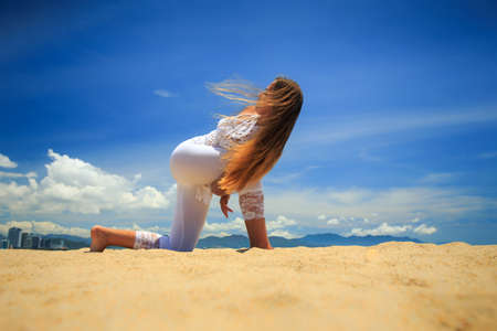 revolved: blonde girl in white lace costume in yoga asana revolved side angle with hand lock on beach against blue sky Stock Photo