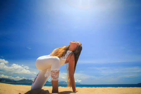revolved: blonde girl in white lace costume in yoga asana revolved side angle on beach against blue sky Stock Photo