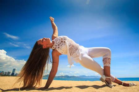 cross leg: blonde girl in white lace costume wind shakes long hair in yoga asana arm balance leg cross on beach against blue sky