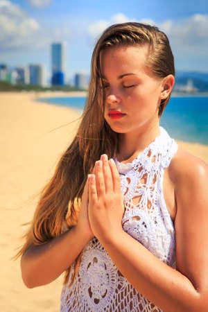 thunderbolt: blonde girl in white lace costume sits in yoga asana thunderbolt on beach against resort city