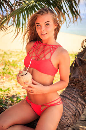 beach blond hair: cute blond longhaired slim girl in red bikini sits on palm trunk holds coconut looks into camera against palm leaf Stock Photo