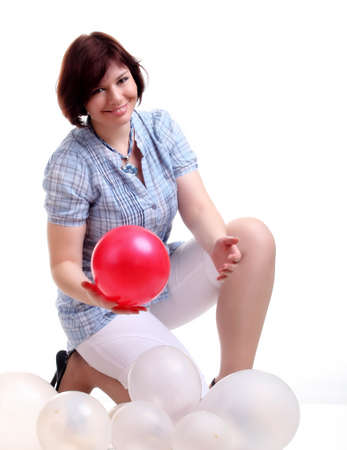 chemise: european brunette girl in blue chemise with red and white balloons squats isolated on white background in studio