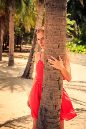 frock: blond slim girl in short red frock looks out of palm trunk and looks into distance against tropical plants