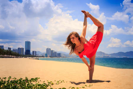 sexual position: blond slim girl in short red frock stands in gymnastic position leg scale on sand beach against azure sea and city