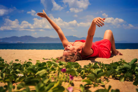 creepers: upper view blond girl in red frock lies on sand lifts hands aside looks upwards near foreground green creepers Stock Photo